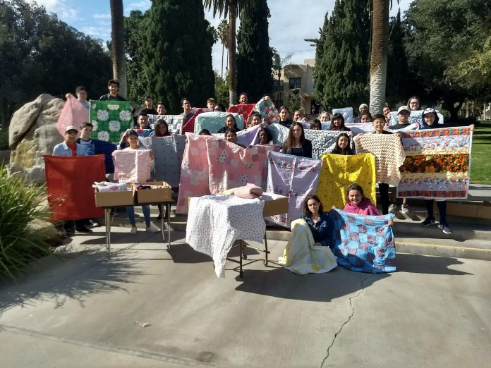 La Sierra University religion class students pose with quilts they helped to box and ship to victims of the Camp Fire in Paradise, California, United States. [Photo: La Sierra University]