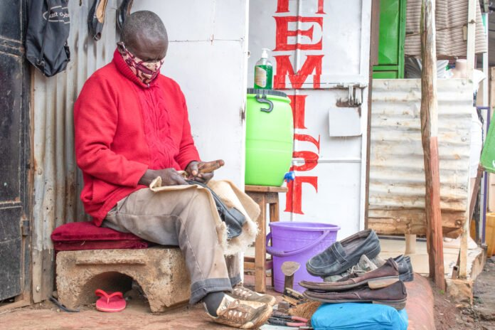 Samuel Onang'o, a cobbler with a disability, is hard at work on several pairs of shoes. [Photo: ADRA Kenya]